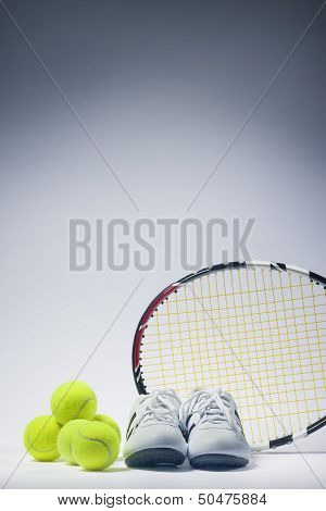 Sports Images Concepts: Tennis Raquet, Tennis Balls And Trainers Against Gray