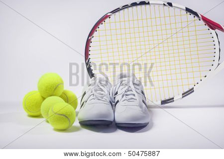 Sports Images Concepts: Tennis Raquet, Tennis Balls And Trainers Against Gray. Vertical Image