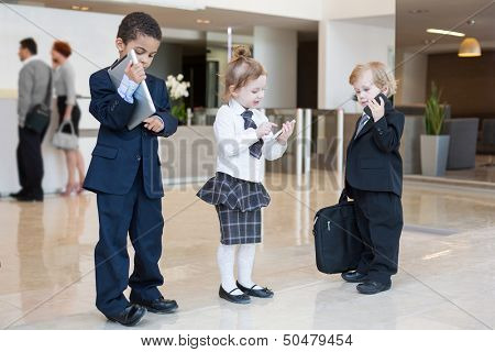 Children with communication devices in the business clothing in the business center with with adults in the background