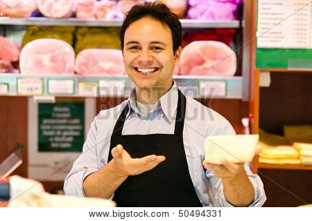 Shop keeper serving cheese