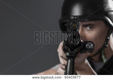 Gunfire, paintball sport player wearing protective helmet aiming pistol ,black armor and machine gun