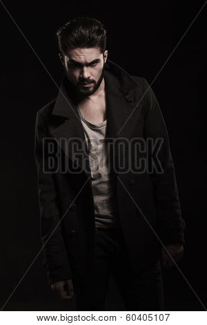 dramatic pose of a young fashion man with beard standing on a dark studio background