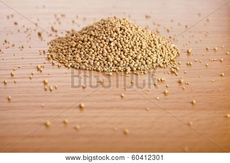 Dry yeast heap in wooden board table background