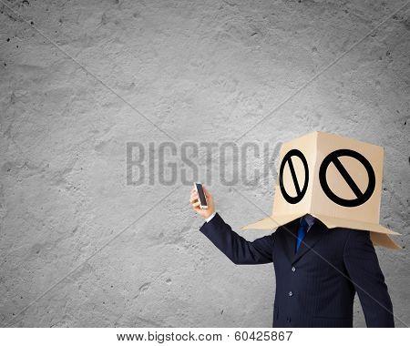 Businessman using mobile phone wearing carton box on head