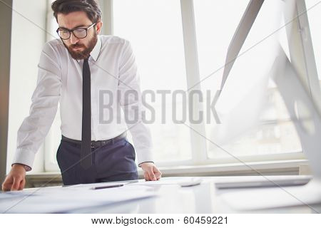Young businessman standing by the window in office and working with papers
