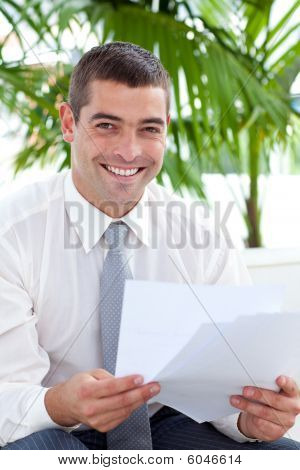 Smiling Businessman Reading Some Documents On Sofa
