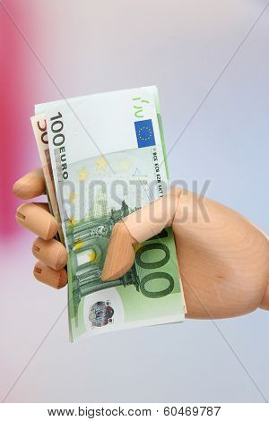 Money in wooden hand, on light background
