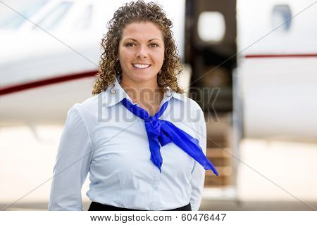 Portrait of beautiful airhostess with private jet in background at terminal
