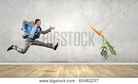 Funny image of businessman chased with carrot
