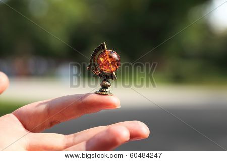 Jewelry miniature of globus on the hand