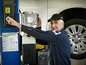 The master auto mechanic shows his experience and expertise with confidence and a friendly demeanor. poster
