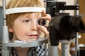 Closeup of male optician's hand checking boy's eye with lens in store poster