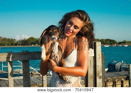 smiling young woman hug little puppy, outdoor shot at seaside, sunny summer day poster