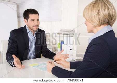Job Interview Or Meeting Situation: Business Man And Woman At Desk.