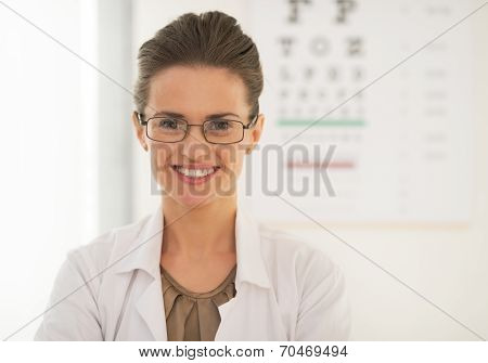 Doctor woman in eyeglasses in front of snellen chart poster