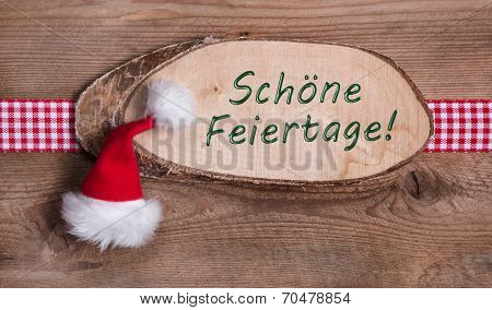 Wooden Sign With Merry Christmas Message And Checkered Ribbon And A Santa Hat On Wooden Background
