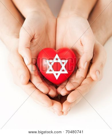religion, christianity and charity concept - family couple hands holding red heart with star of david symbol