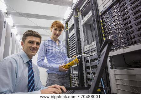 Team of technicians using digital cable analyser on servers in large data center poster