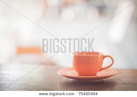 Mini Orange Coffee Cup On Wooden Table