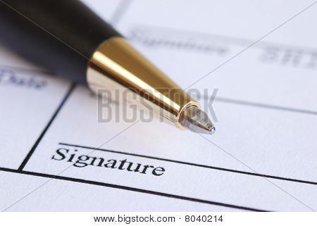 Sign the name on a paper with a pen
