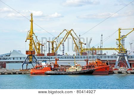 Bunker ship and tugboat under port crane