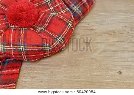 Traditional Scottish Red Tartan Bonnet And Scarf On Wood Board
