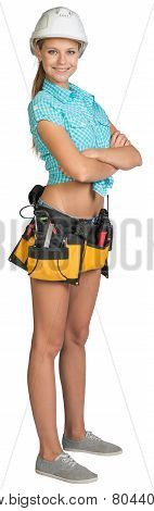 Pretty girl in helmet, shorts, shirt and tool belt with tools. Full length