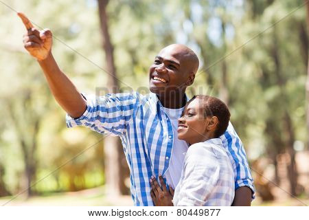 cheerful young african couple in the forest bird watching