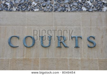 Exterior Signage Of Justice Law Courts On A Stone Wall With Flint Stones