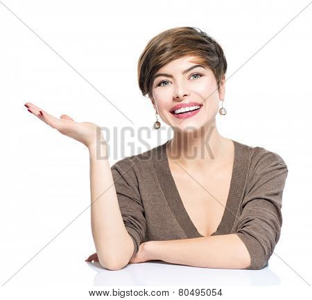 Young smiling beauty woman with bob showing empty copy space on the open hand palm on white background. Happy girl presenting point by raised hand for text. Gesture for selling product, advertisement.