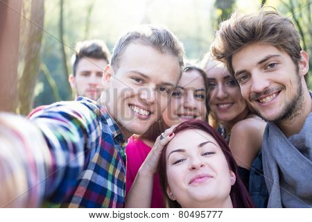 Young people having good time together in park on river and taking selfie poster