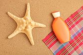 A view of a sea star and sun cream on a sandy beach poster