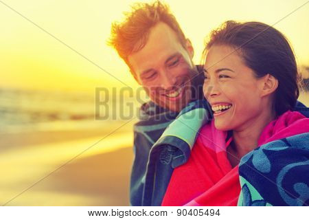Bathing romantic couple with towel on beach sunset. Portrait of happy young interracial couple embracing each other having fun outdoors during holidays vacation travel. Asian woman, Caucasian man.