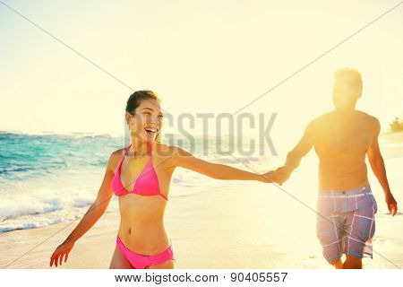 Laughing happy romantic couple summer vacation beach fun. Joyful multi-ethnic young couple laughing elated together on tropical beach holiday on resort. Mixed race Asian woman and Caucasian man.