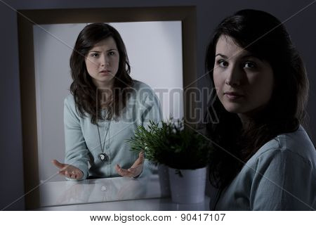 Young woman with mental disorder sitting at the desk poster