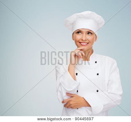cooking and food concept - smiling female chef, cook or baker dreaming over gray background