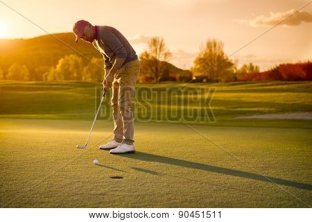 Male golf player putting at green with beautiful fairway at sunset.