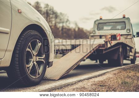 Loading broken car on a tow truck on a roadside
