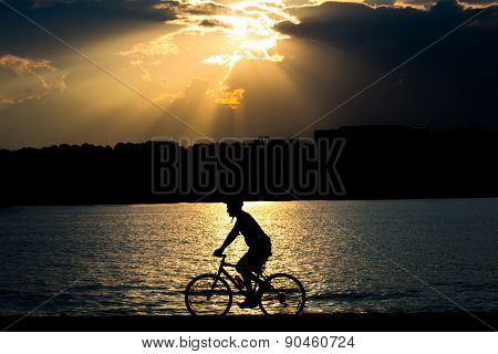 Silhouette of a cyclist in a dramatic clouds background - Washington DC, Potomac Riverside