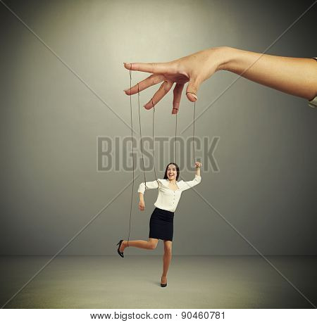 womans hand manipulating puppet over dark background