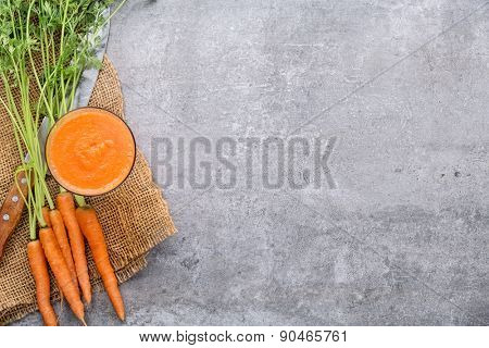 Carrots and carrots juice on stone background