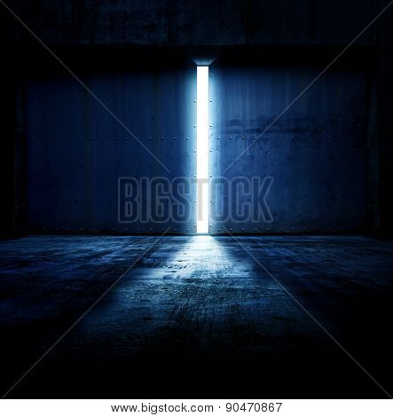 Light coming in through opening of heavy steel doors .Large metal doors of an hanger like building opening and blue light coming in.