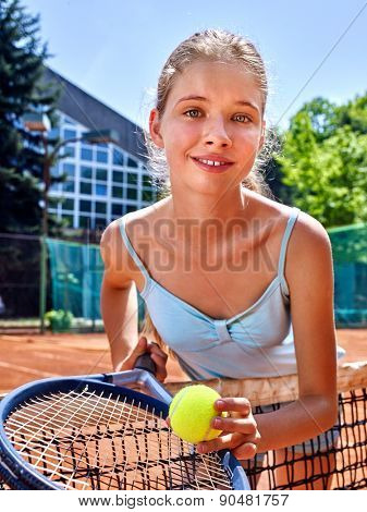 Girl sportsman with racket and ball near net on  tennis court. Green tree ang blue sky on background. Looks over her shoulder. Stadion on background.