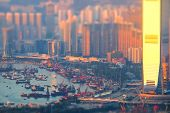 Tilt shift aerial view panorama of Hong Kong skyline and Victoria Harbor at sunset. Travel destinations poster