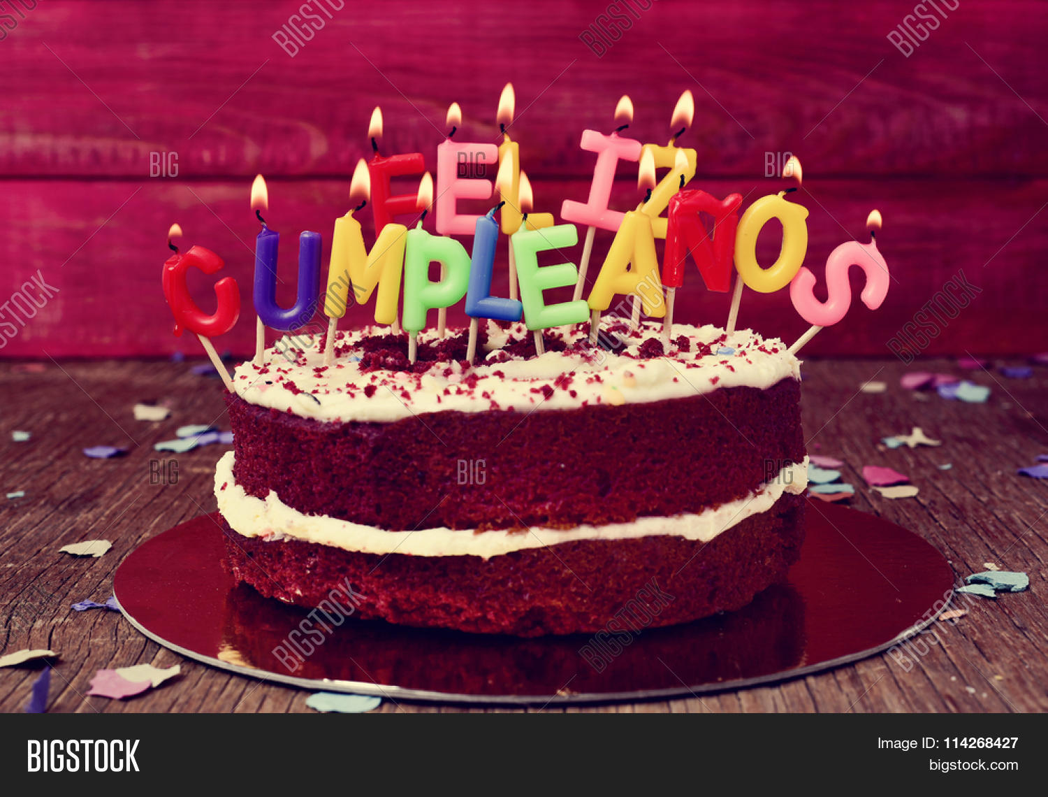 A Cake Topped With Some Lit Letter Shaped Candles Forming The Text Feliz Cumpleanos