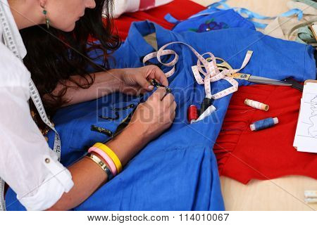 Female Fashion Designer Sewing Accessories To Blue Retro Style Dress