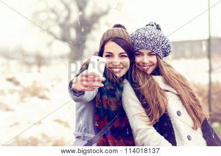 Two happy teenage girlfriends taking a selfie on snowy winter day