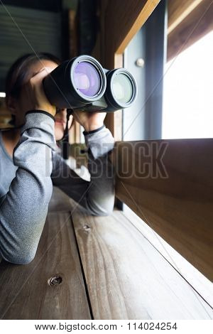 Woman looking though binocular at wooden house