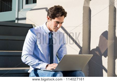 Young businessman sitting on stairs and working on laptop. Young man sitting on the steps outside and working at laptop, checking email. Man using laptop while sitting on staircase on a sunny day.