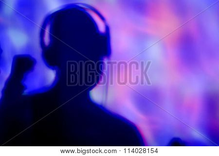 the silhouette of a young man wearing headphones in a dance club with colorful lights